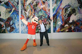 Sebastian the Ibis and UM alum and renowned Miami artist Xavier Cortada celebrate the unveiling of the digital tapestry Cortada created for the Student Activities Center's third floor.