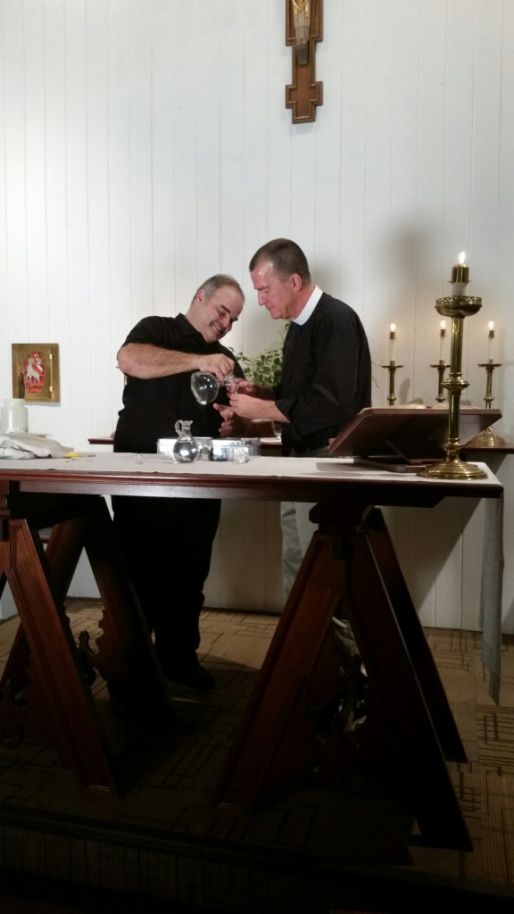 Fr. Dave Collins and Xavier Cortada pour Antarctic water into vials for South Pole Communion.